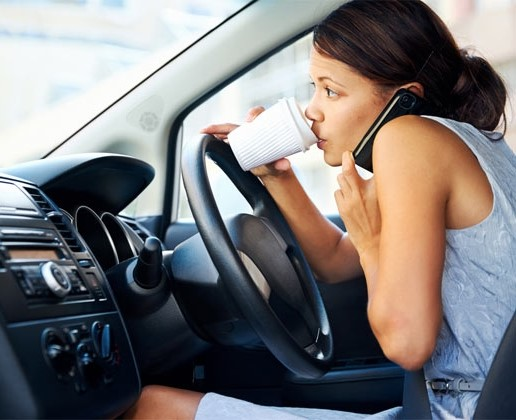 woman driving sipping coffee and on phone
