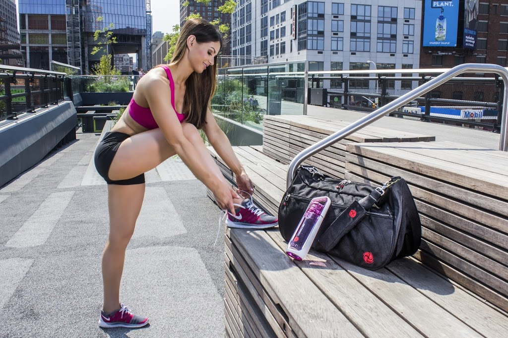 woman tying shoes while jogging