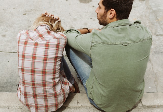 man and woman sitting regretting